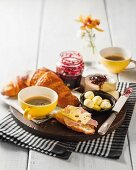 A breakfast platter with croissant, cheese, jam, butter and coffee
