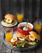 Bread rolls with a spicy bean sauce, eggs, rocket and tomatoes for brunch
