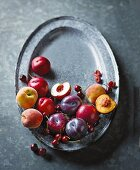 Fresh plums, peaches and cherries on a metal tray