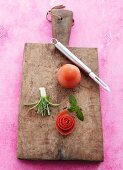 Homemade vegetable flowers, mint leaves and tomatoes on a wooden chopping board