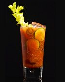 A Bloody Mary cocktail in a glass on a black surface