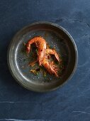Two sauteed prawns in metal dish (seen from above)