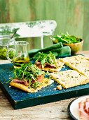 Olive oil tarts with proscuitto and pesto