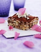 A slice of triamisu garnished with grated white chocolate and rose petals