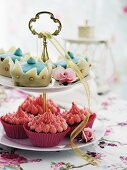 Cupcakes with pink cream and blue marzipan decorations on a cake stand