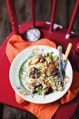 Fried chicken liver with vegetable rice on a red chair