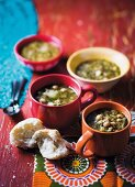 Onion and chickpea soup with white cabbage in cups and bowls