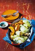 White cabbage roulade with oven-roasted butternut squash in a baking dish