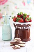 Milk chocolate, fresh strawberries and a bottle of milk (ingredients for a chocolate fondue)