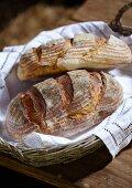 Zwei rustikale Brote im Brotkorb auf Holztisch
