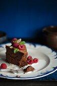 A slice of dark chocolate cake with raspberries, mint and liquid cream