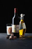 A symbolic image of a gourmet investment: pralines, red wine, milk and olive oil with money
