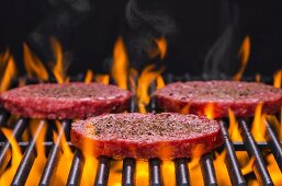 Raw hamburgers seasoned with salt and pepper on a flaming barbecue