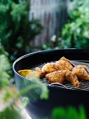 Grilled chicken bits and lemons on a barbecue in a garden