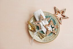 Decorated gingerbread stars and silver cutlery on plate as table decorations