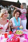 Three women having a picnic outside