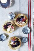 Pistachio and coconut tartlets with black cherries and figs
