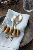 Silver spoons on linen napkin held in ring threaded with acorns