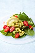 Guacamole on a mixed leaf salad with cherry tomatoes