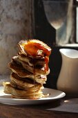 A stack of pancakes dripping with maple syrup
