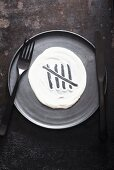 A grey plate with cutlery and a dollop of yoghurt with five tally marks