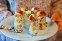 Potato salad with salami and quail's eggs in glasses