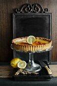 lemon tart on a glass cake stand with fresh lemons