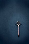 A spoonful of black caviar on a dark-blue surface