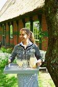 A woman serving elderflower spritzers in a garden