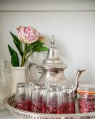 Silver teapot, Oriental tea glasses and peony in vase on tray