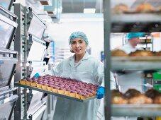 Bäckerin hält Backblech mit frisch gebackenen Muffins in der Kuchenfabrik