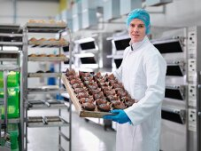 A baker holding a tray of cakes in a cake factory