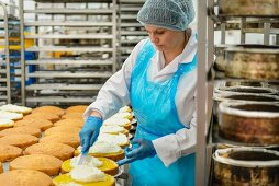 A baker spreading filling onto cakes in a cake factory