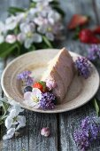 A slice of butter cream cake on a plate decorated with flowers and berries