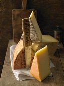 Verschiedene Käsesorten auf Holzbrett mit Messer