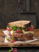 Graubrot-Burger mit mit Bergka?se, Lammhacksteak, gegrilltem Apfel und su?ß-sauren Zwiebeln