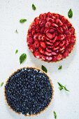 Two whole round fruit tarts with strawberries and blueberries (seen from above)