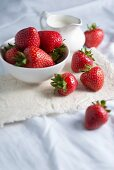 Fresh strawberries in a bowl with a jug of cream on a linen cloth