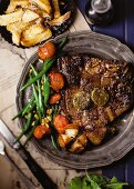 A T-bone steal with anchovy butter, green bean and tomato medley, chips and chermoula