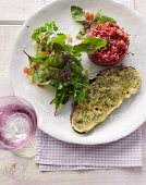 French toast made from country bread with beef tatar and wild herb salad