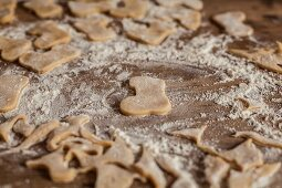 Cut-out biscuits and leftover pastry on a floured work surface