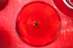 A view from above of a red drinking glass garnished with a cocktail tomato