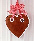 Lebkuchenherz mit schlichtem Zuckerguss an rot-weiß kariertem Schleifenband