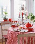 Rot-weiss gedeckter Kaffeetisch mit karierter Tischdecke, Kerzenleuchter und alten Stühlen