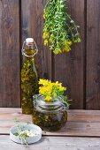Johanniskrautöl und zum Trocknen aufgehängtes Johanniskraut