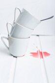 A stack of three white tea cups next to a splash of fruit tea