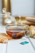 Peppermint tea in a glass cup served with biscuits and pralines