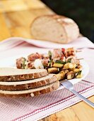 Slices of rye bread with vegetable salad and grilled skewers