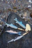 Various fishing hooks on a rocky beach