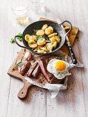 A rib-eye steak with a fried egg and fried potatoes
